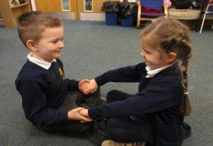 Two children sat holding hands